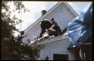 State troopers arresting a protester on the roof of the home of war tax resisters Randy Kehler and Betsy Corner