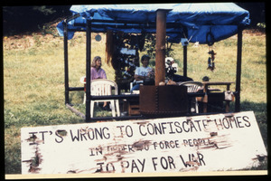 Supporters at the home of war tax resisters Randy Kehler and Betsy Corner seated behind a sign reading 'It's wrong to confiscate homes in order to force people to pay for war'