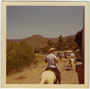 Campesinos on horseback riding past Brigade buses