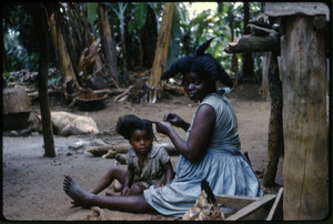 Sao Tome and Principe: 'femme et enfant à l'Santomene implanté à Principe' (woman seated on the ground in a village, braiding a child's hair)