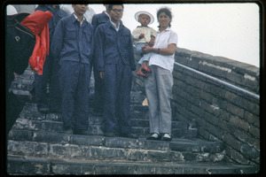 Group standing atop the mist-shrouded Great Wall