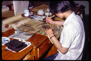 Arts and crafts factory: woman painting scenery in ink on a scroll