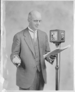 Gleason L. Archer (President, 1937-1948, and Founder of Suffolk University) standing in front of NBC microphone, reading from script