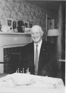 Gleason L. Archer (President, 1937-1948, and Founder of Suffolk University) in front of birthday cake at his 79th birthday party, 3rd floor living room, Suffolk Law School