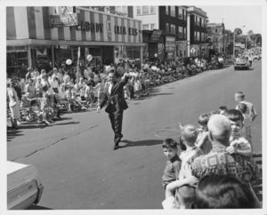 John Joseph Moakley walking and waving to crowd at a parade in South Boston (MA), 1960s