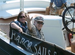 Suffolk University Dean Michael Ronayne (CAS) waving from a boat at the 50th reunion for the class of 1951