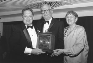 Suffolk University Professor Alexander Cella (Law) receiving a clock from Dean Paul R. Sugarman (Law) and another attendee at a law school event