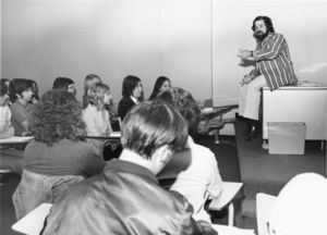 Suffolk University Professor Malcolm Barach (CAS) seated on top of desk, lecturing to students in classroom