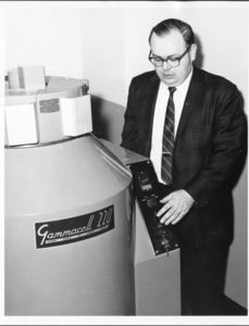 Suffolk University Dean Michael R. Ronayne (CAS, 1972-2004) poses with a Gammacell 220, a self-contained research irradiator