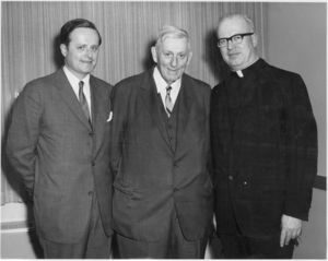 Suffolk University Dean John E. Fenton, Jr., Suffolk University President John E. Fenton (1965-1970), and unidentified priest at the 1969 commencement