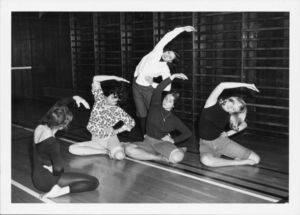 Suffolk University students doing stretching exercises in a physical education class