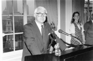 Suffolk University Dean John F. Brennan (SOM 1991-2001), standing behind podium with microphones