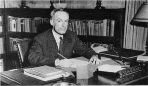 Suffolk University Dean Lester R. Ott, Lester (CAS 1945-1949), seated behind desk