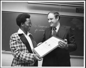 Timothy Whelan accepting an award from Mohamed Barrie of the International Student Association, 11/1977