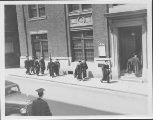 Graduates walking on Derne Street at the Suffolk University's first Baccalaureate exercises, 6/13/1937