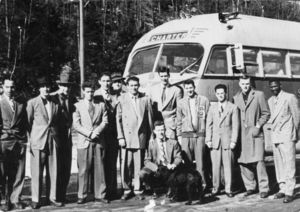 Suffolk University's basketball team and Coach Charlie Law posed in front of bus, 1949