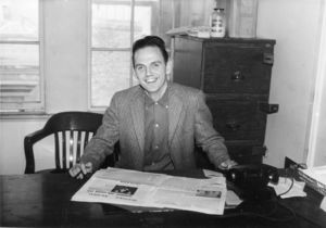 Suffolk University student Bud O'Brien, sports editor for the Suffolk Journal, seated at desk, 1958