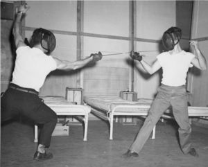 Two Suffolk University students fence on stage with cots in background, possibly a theatre performance