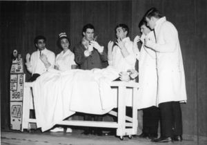 Suffolk University students perform onstage for a theater production, dressed in white medical lab coats