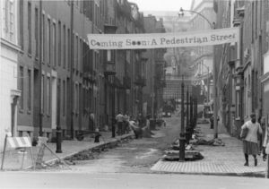 """View of Temple Street and Suffolk University banner that reads: """"Coming soon: a pedestrian street"""""""