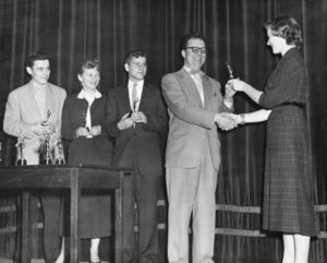 A student presents an award to Director of Student Affairs Director John V. Colburn at Suffolk University's Recognition Day ceremony, circa 1953