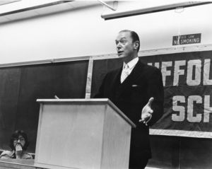 Roger Moore speaking in a Suffolk University classroom from behind podium