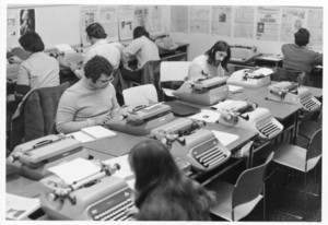 Overhead shot of Suffolk University students working at typewriters, newspapers hanging on walls