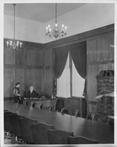 Catherine Carraher (secretary of Suffolk Law School) and Suffolk University President Gleason L. Archer (at desk) in the Archer Building (20 Derne Street) Trustees Room