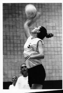 A Suffolk University women's volleyball player spikes the ball, circa 2000