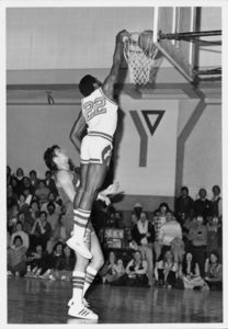 Suffolk University men's basketball player Donovan Little dunks the ball for two points during a game, circa 1978-1979