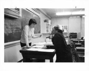 Suffolk University professor Beatrice L. Snow (Biology), standing behind desk in classroom, talking with a student