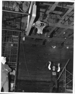Suffolk University Athletics Director James E. Nelson (1978-2013), testing basketball hoop as new gym is completed