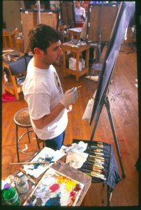 A Suffolk University student paints at an easel during a NESAD painting class