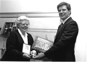 Suffolk University Law School Librarian and alumnus Patricia I. Brown donating items related to her career in the All-American Girl's Professional Baseball League to Athletics Director James E. Nelson (1978-2013)