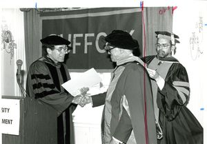 Suffolk University Professor Daniel H. Perlman shaking hands with Malcolm Forbes, and Dean Richard McDowell at the 1987 commencement