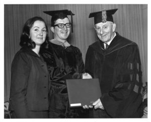 James Griffin, with wife Kathy Griffin, receives diploma from President John E. Fenton (1965-1970) at the 1970 Suffolk University commencement