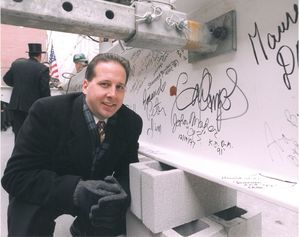 Attendee poses in front of signed beam at Suffolk University Law School's Sargent Hall (120 Tremont Street) topping off ceremony