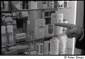 Bill Baird, contraception rights advocate, standing in a pharmacy, pointing at contraceptives in a medicine case and holding up the day's newspaper (close-up of Baird's hand)