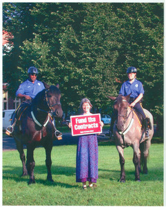 Lisa Lipshires with protest sign 'Fund the contracts,' standing between two mounted police