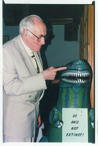 Sidney Lipshires (left) and inflatable dinosaur at his eightieth birthday party: '80 and not extinct'