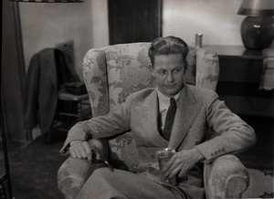 Carl Miller (?), seated with drink in hand