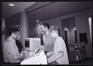 Newton Free Library, Newton, MA. Communications & Programs Office. Photograph of three people at a library service desk