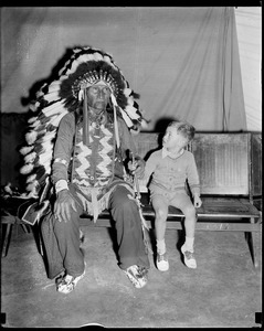 Boy holds hands with Indian at circus