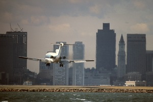 Arriving jetliner at Logan Airport and downtown skyline, East Boston