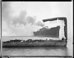 Burning wooden ship 'Wakanna' through ruin of another. Scrapped, Boston Harbor.