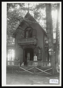 Steep pitched roof, victorian cottage with upper level balconies showing man, woman, and dog on porch, Asbury Grove, So. Hamilton, Mass
