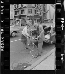 Dr. Paul Dudley White unloading bicycle from station wagon for 5-mile ride from Boston Common to Jamaica Pond