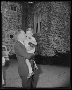Henry Cabot Lodge, Jr. holding grandson with toy truck outside his Beverly home