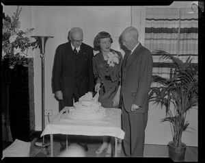 Tenley Albright, with two men, cutting cake decorated with figure skates