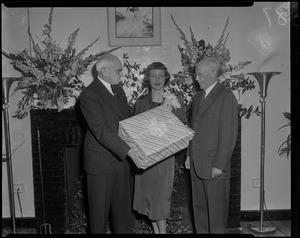 Tenley Albright with two men, holding a wrapped gift box